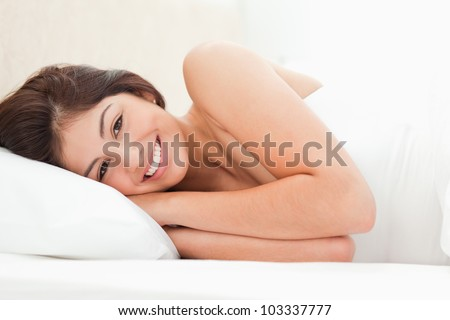 A woman lying on a bed, eyes open, smiling, her hands under her head. - stock photo