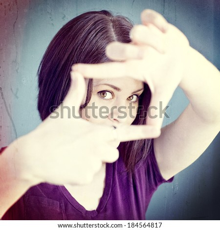 A woman making a frame with her fingers, instagram style - stock photo