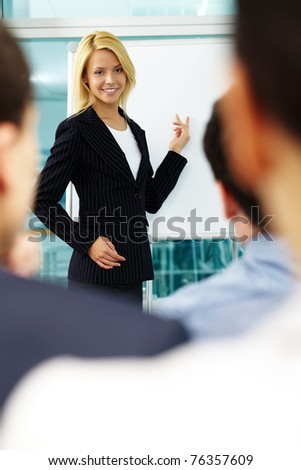 A woman manager pointing at whiteboard with colleagues listening to her - stock photo