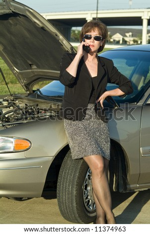 A woman on a cell phone standing by an automobile with the hood up. - stock photo