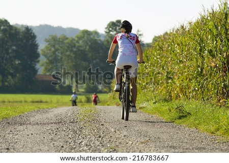 A woman on a cycle catching up with her friends in front. - stock photo
