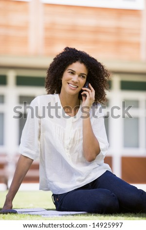 A woman on her mobile phone sitting on a campus lawn - stock photo