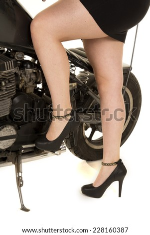 A woman on her motorcycle showing off her legs. - stock photo