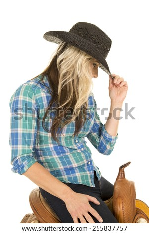 A woman on her saddle touching the brim of her hat looking down. - stock photo