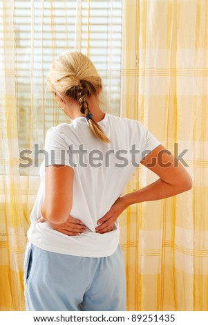 a woman on the morning after waking up the pain. - stock photo