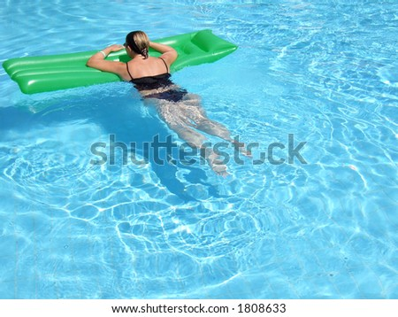 A woman on vacation relaxes in the pool on a summer day - stock photo