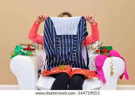 A woman opening Christmas presents to discover she got an apron and some underwear. - stock photo
