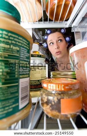 a woman peering into an open fridge - domestic series - stock photo