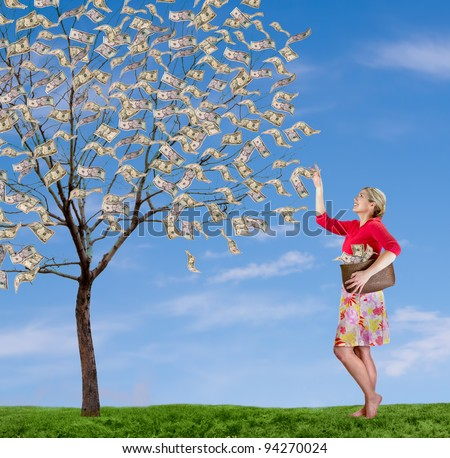 a woman picking money off of a money tree,  with a blue sky and grass. - stock photo
