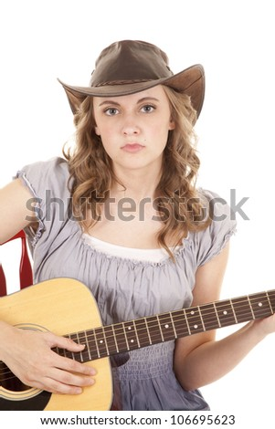 A woman playing her guitar with a serious expression on her face while wearing her cowgirl hat. - stock photo