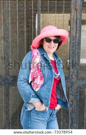 A woman poses against a metal security gate while wearing a colorful pink hat, vibrant scarf and sunglasses. - stock photo