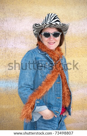 A woman poses against a yellow wall while wearing vintage tiger striped sunglasses and hat. - stock photo