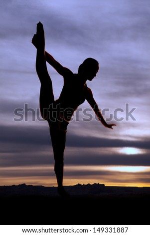 a woman pulling her leg up showing off her flexibility. - stock photo