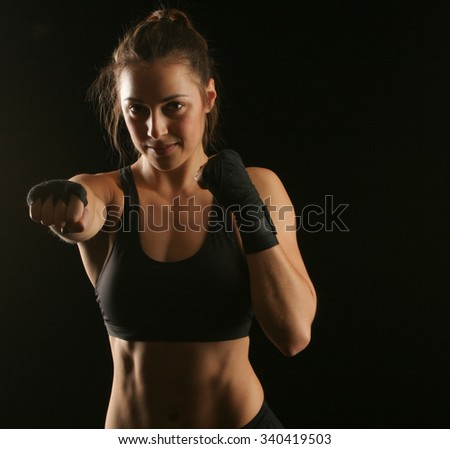 A woman punching with fist wraps on - stock photo