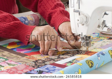 A woman quilter is cutting excess thread on a sewing machine. - stock photo