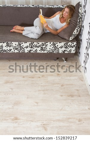 A woman reading a book and smiling as she lays on sofa in room - stock photo