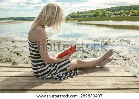 A woman reading a book at the beach - stock photo
