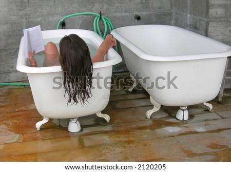 A woman reads while soaking in a spa tub - stock photo