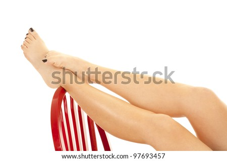 A woman relaxing  and putting up her bare feet and legs up on the back of a red chair. - stock photo