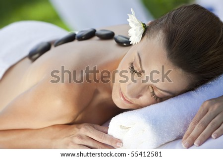 A woman relaxing at a health spa while having a hot stone treatment or massage - stock photo