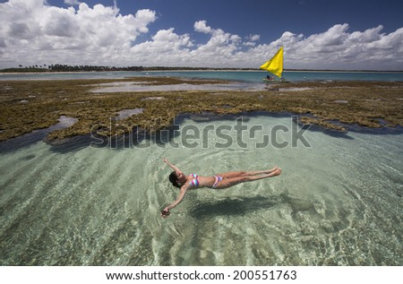 A woman relaxing in a natural pool with a yellow boat on background in Porto de Galinhas, Brazil. - stock photo