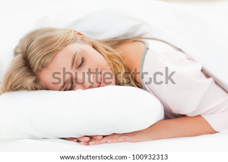 A woman resting in bed with her head on the pillow and her hands underneath it and her eyes are closed. - stock photo