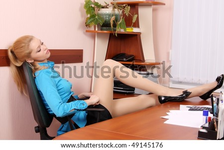 A woman rests, throwing his feet on the table - stock photo