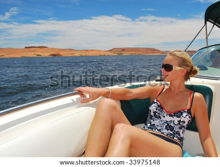 A woman riding on a boat at lake powell - stock photo
