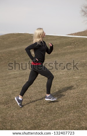 a woman running up a hill where there is still snow. - stock photo