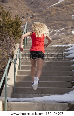 A woman running up the stairs in the outdoors with snow all around her. - stock photo