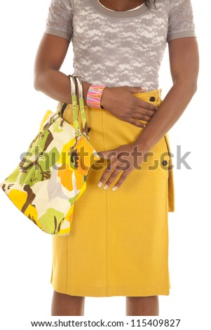 A woman's body in her yellow skirt holding on to her yellow and green purse. - stock photo