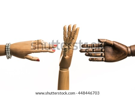 A woman's hand and one hand of black man meet. A white hand opposes. On white background. With copy space. - stock photo