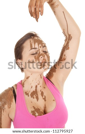 A woman's hand dripping mud onto her face. - stock photo