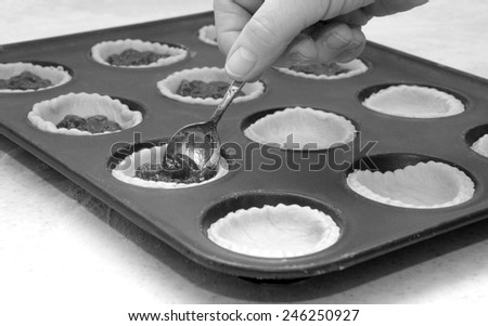 A woman's hand holding a teaspoon as she fills jam tarts - monochrome processing - stock photo