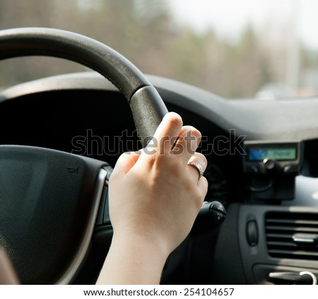 A woman's hand on the steering wheel of the car - stock photo
