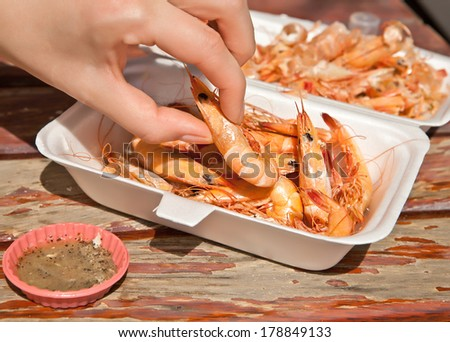 A woman's hand takes the ready-to-eat shrimp - stock photo