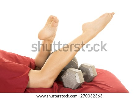 a woman's legs laying on a set of work out weights. - stock photo