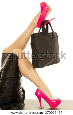 A woman's legs up in the air with pink heels on her feet. - stock photo