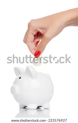 A woman's manicured hand dropping a coin into a piggy bank isolated on white. - stock photo