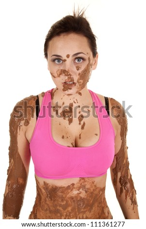 A woman's top half of her body covered in mud with a serious expression on her face. - stock photo