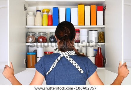 A woman seen from behind opening the doors to a fully stocked pantry. The cupboard is filled with various food stuff and groceries all with blank labels. Horizontal format the woman is unrecognizable. - stock photo
