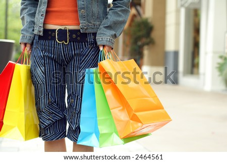 A woman shopping in a mall carrying shopping bags - stock photo
