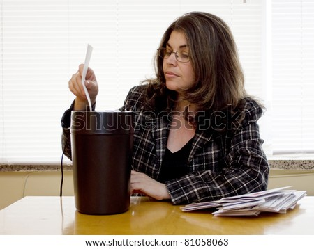 A woman shreds her personal information - stock photo