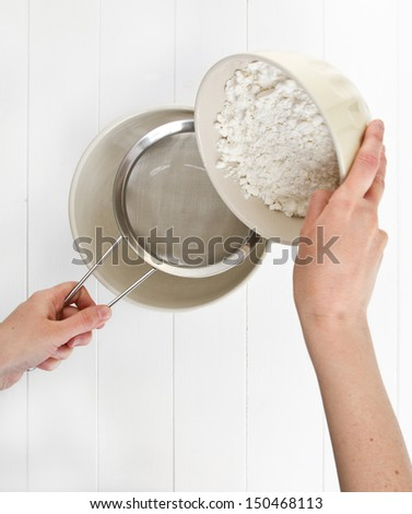 A woman sifts white flour through a metal sieve into a ceramic mixing bowl, on white wood. - stock photo