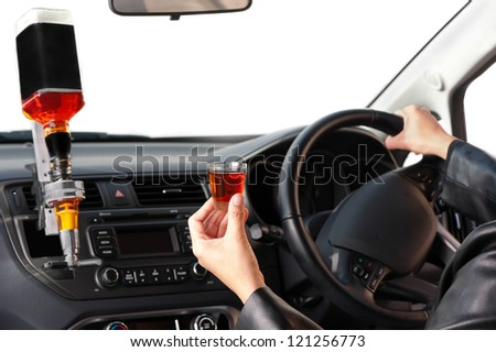 A woman sits behind a steering-wheel of a car specially converted for her to drink whilst driving. - stock photo