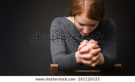 A woman sits on a wooden chair and prays to God. - stock photo