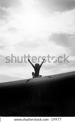 A woman sits triumphantly on top of a pristine sand dune raising her arms to the sky and the sun. - stock photo