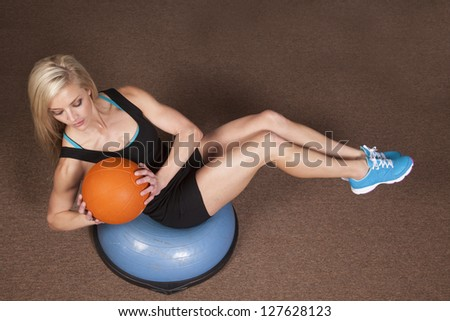 a woman sitting and doing a twist with a weighted ball - stock photo