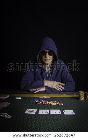 A woman sitting at a poker table wearing sunglasses and hoodie playing cards with a black background - stock photo