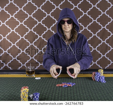 A woman sitting at a poker table wearing sunglasses and hoodie playing cards with a brown background - stock photo